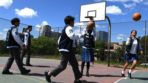 Parramatta High School year 12 students play basketball on the school grounds.