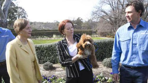 Then Prime Minister Julia Gillard and her dog Reuben pose for a photograph with Lodge gardeners on the grounds. (AAP)