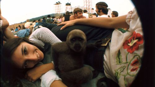 An unidentified girl smiles while her pet monkey sits in the middle of her group at the Woodstock Music Festival, Bethel, New York.