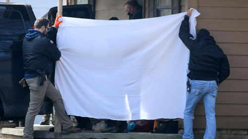 Investigators block the public's view as bodies are removed from the scene of a suspected mass homicide where at least 5 children were slain Tuesday, February 2.