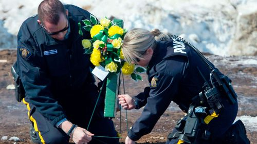 Members of the Royal Canadian Mounted Police lay flowers at the intersection of a crash site near Tisdale, Saskatchewan. (AP).