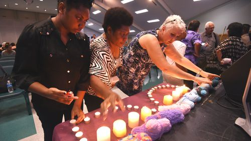 Mourners light candles at a service for the children dead in an alleged knife attack in Cairns. (AAP)