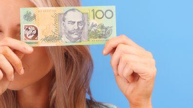 Woman holding Australian $100 note