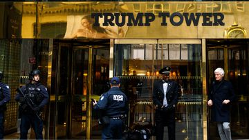 A doorman talks with security personnel at the front entrance of Trump Tower in New York.