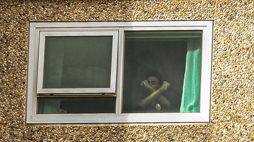 A man living in the Flemington Public housing flats is seen making a gesture with his arms crossed.