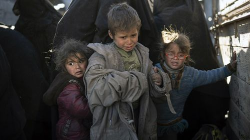 Women and children exit the back of a truck as they arrive at a screening area after being evacuated out of Baghouz.