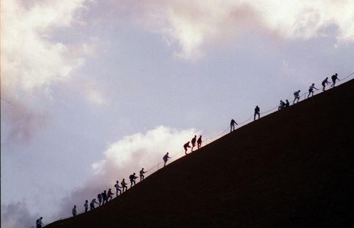 File photo shows tourists climbing Uluru at sunrise.