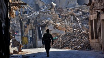A Syrian pro-government fighter walks past damaged buildings in the Bab al-Nasr district of Aleppo's Old City on December 9, 2016. (AFP)