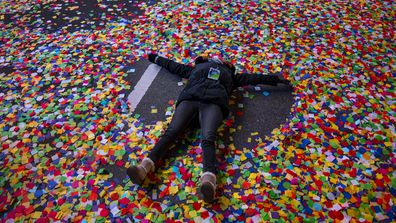 Jaclyn Bernstein, of New York, lies in confetti after the Times Square New Year's Eve Ball dropped in Times Square.