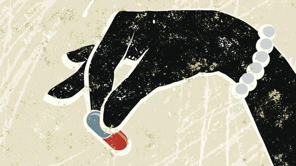 Woman's hand holding pill
