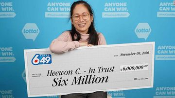 Heewon (Theresa) Choi holds up a giant cheque for $6 million (A$6.3 million) after winning the lottery.