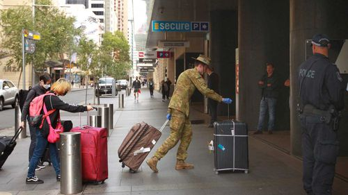 Australians returning from overseas are led into the Hilton Hotel in the Sydney CBD.