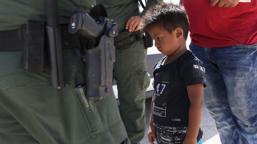 A boy and father from Honduras are taken into custody by US Border Patrol agents near the US-Mexico Border on June 12, 2018 near Mission, Texas.