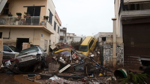 A man looks out from his home over piles of vehicle. (AAP)