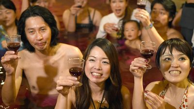 Guests hold their glasses as they enjoy a 'wine bath' at the hot springs resort near Tokyo in Japan. (AAP)
