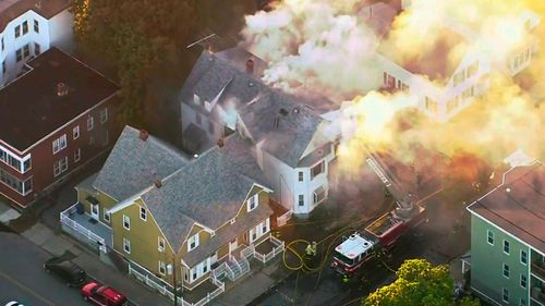 Firefighters battle a large structure fire after residents fled in panic.