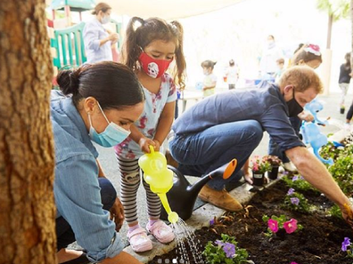 Harry and Meghan planting a garden at a preschool.