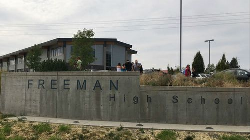 People gather outside of Freeman High School after reports of a shooting at the school in Rockford, Washington. (AAP)