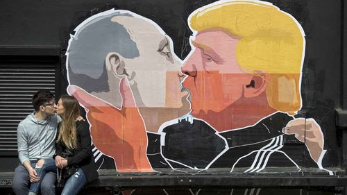 A mural on a street in Vilnius, Lithuania, showing Vladmir Putin and Donald Trump in an embrace. (AP)