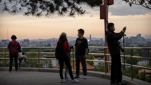 People wearing face masks to protect against the spread of the new coronavirus stand on a hilltop at a public park in Beijing, Saturday, April 25, 2020.