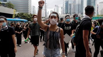 Protesters march to surround the police headquarters in Hong Kong.