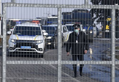 A motorcade with police cars and busses with passengers from the Ukrainian aircraft chartered by the Ukrainian government for evacuation from the Chinese city of Wuhan, leave the the gate upon their landing at airport outside Kharkiv.