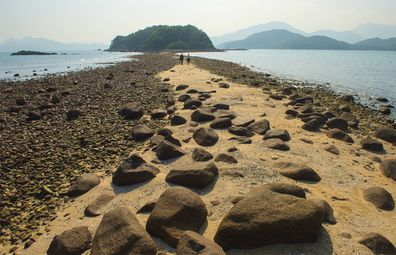 The tombolo walkway emerges at low tide on Sharp Island, one of Hong Kong's UNESCO Global Geoparks.