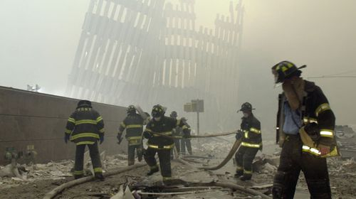Firefighters work beneath the destroyed mullions, the vertical struts which once faced the soaring outer walls of the World Trade Center towers. (AAP)