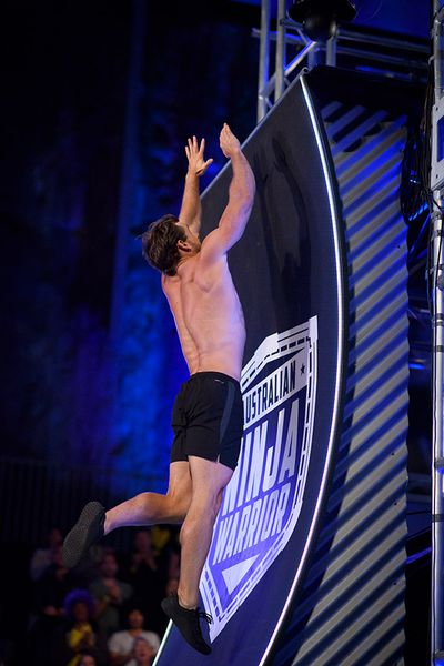 Nathan McCallum leaps for the ledge of the Warped Wall.