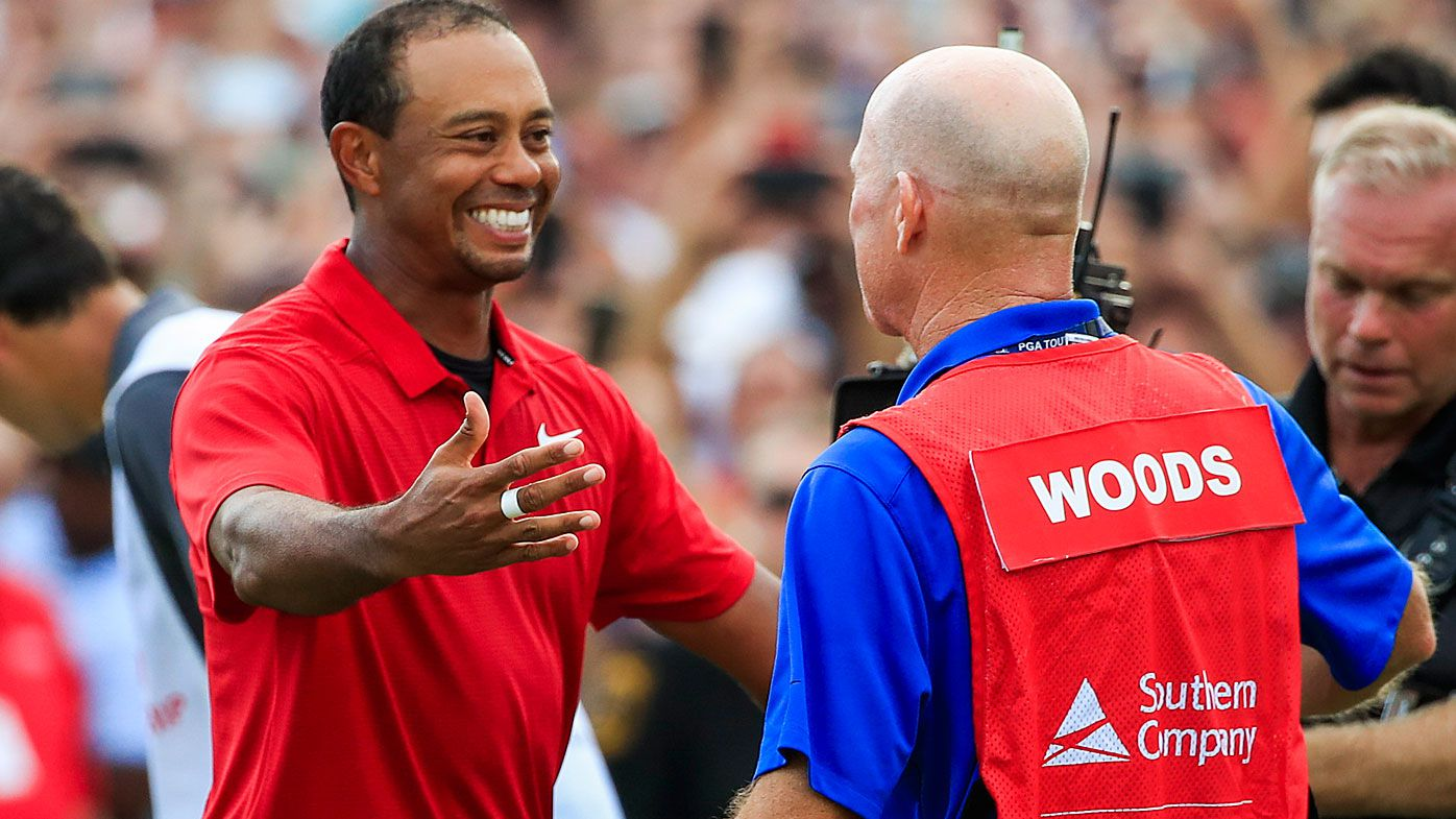 Tiger Woods celebrates with his caddy