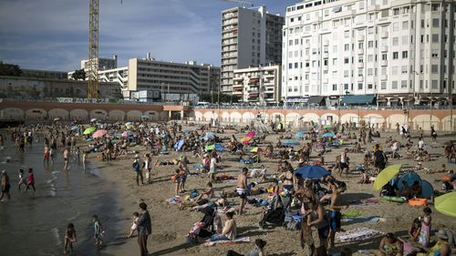 Beachgoers enjoy the sun at the Plage des Catalans in Marseille, southern France (Photo: July 25, 2020