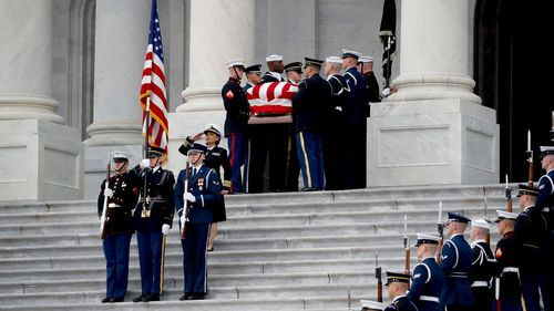 The casket of George HW Bush is taken from the Capitol Rotunda.