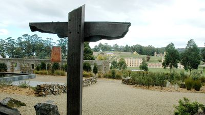 A timber cross memorial to the 35 people killed in the 1996 Port Arthur massacre overshadows the shell of the Broad Arrow Cafe, where 20 of the victims died,