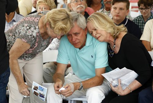 Carl Hiaasen, center, brother of Rob Hiaasen, one of the journalists killed in the shooting at The Capital Gazette newspaper offices, is consoled by his sister Judy, right, and an unidentified mourner during a memorial service (AP Photo/Patrick Semansky