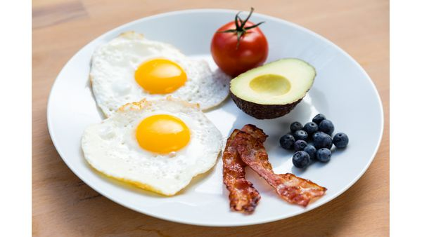 High fat low-carb breakfast with eggs, tomato, avocado, bacon and blueberries. iStock