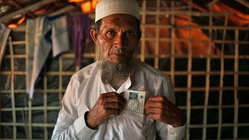 Abdul Jabar, 61, holds an identification card belonging to his late son whom he said was slain by members of Myanmar's armed forces. (Photo: AP).