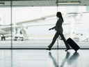 Woman business traveller walks with luggage at the airport