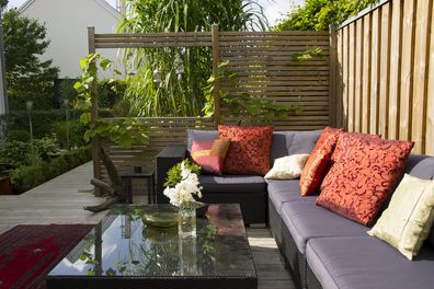 A modern patio with an outdoor wicker sofa.