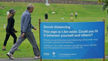 People exercise at a park which displays social distancing signage in Melbourne, Saturday, April 18, 2020.