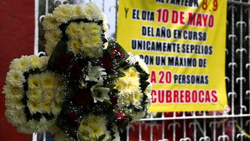 """A funeral wreath is displayed at the entrance of the San Isidro cemetery near a sign that reads in Spanish: """"There will be no access to the cemetery on May 8, 9 and 10"""" in Mexico City, Friday, May 8, 2020.  (AP Photo/Fernando Llano)"""