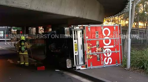 Coles driver 'follows GPS' and flips truck on Sydney road