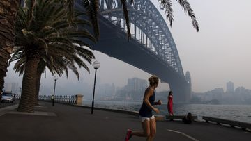 A jogger runs along the waterfront as smoke haze from bushfires sits over the harbour bridge.