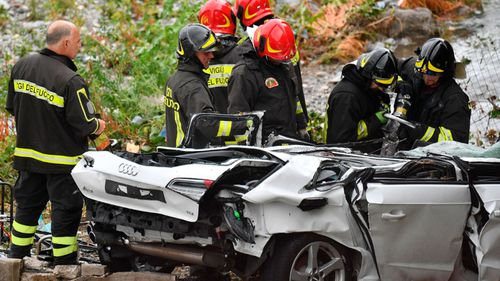 Rescue workers examine a crushed car after the bridge collapse in northern Italy.