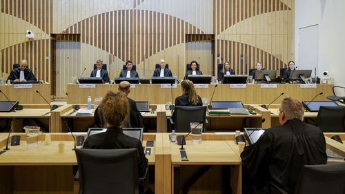 Presiding judge Hendrik Steenhuis, rear, fourth from left, opens the court session as the trial resumed at the high security court building at Schiphol Airport, near Amsterdam, Monday, June 8, 2020, for three Russians and a Ukrainian charged with crimes including murder for their alleged roles in the shooting down of Malaysia Airlines Flight MH17 over eastern Ukraine nearly six years ago.