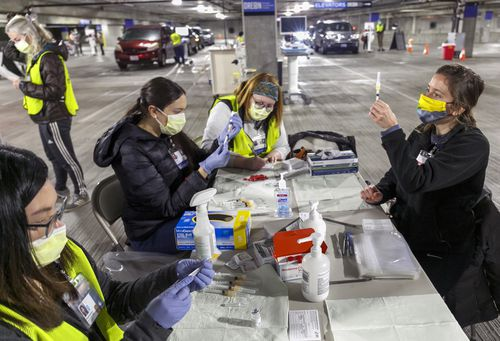In this January 10 file photo Medical professionals from Oregon Health & Science University load syringes with the Moderna COVID-19 vaccine at a drive-thru vaccination clinic in Portland, Oregon.