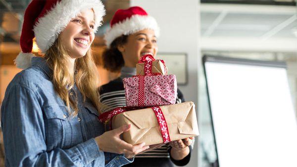 Colleagues carrying Secret Santa presents