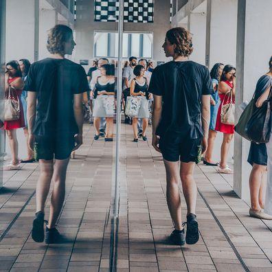 Man looking in mirror, walking