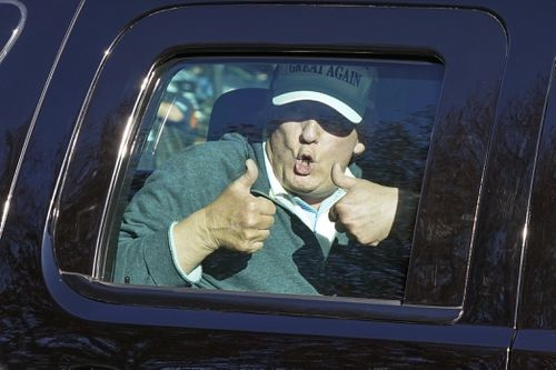 President Donald Trump gives two thumbs up as he departs after playing golf at the Trump National Golf Club.