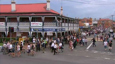 <p>Thousands of mourners lined the streets of Macksville to bid one last goodbye to cricketer Phillip Hughes. </p><p> A guard of honour that included Australian cricket captain Michael Clarke and Prime Minister Tony Abbott overflowed from the local high school to send Hughes' coffin on its journey through the tiny NSW mid coast town of 2567 residents. </p><p> A sombre procession of people stretching hundreds of metres walked behind a hearse carrying the local hero in a final mark of respect. </p><p> Earlier, Hughes' family invited the entire town of Macksville to attend their son's funeral, saying that each and every one of them were part of his cricketing career. </p><p> Hughes' parents Greg and Virginia were supported by their children as Clarke and fellow pallbearers Greg and Jason Hughes, Corey Ireland, Mitchell Lonergan, Matthew Day, Aaron Finch and Tom Cooper, carried their fallen friend after the moving service.</p><p>Click through to watch video of Macksville's final farewell.</p>
