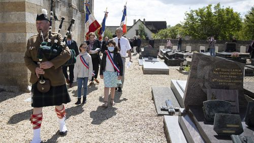 British expatriate Steven Oldrid, right, is led by a bagpiper as he directs a D-Day ceremony of laying flowers and wooden crosses for WWII dead at the local war cemetery in Benouville, Normandy, France on Saturday, June 6, 2020